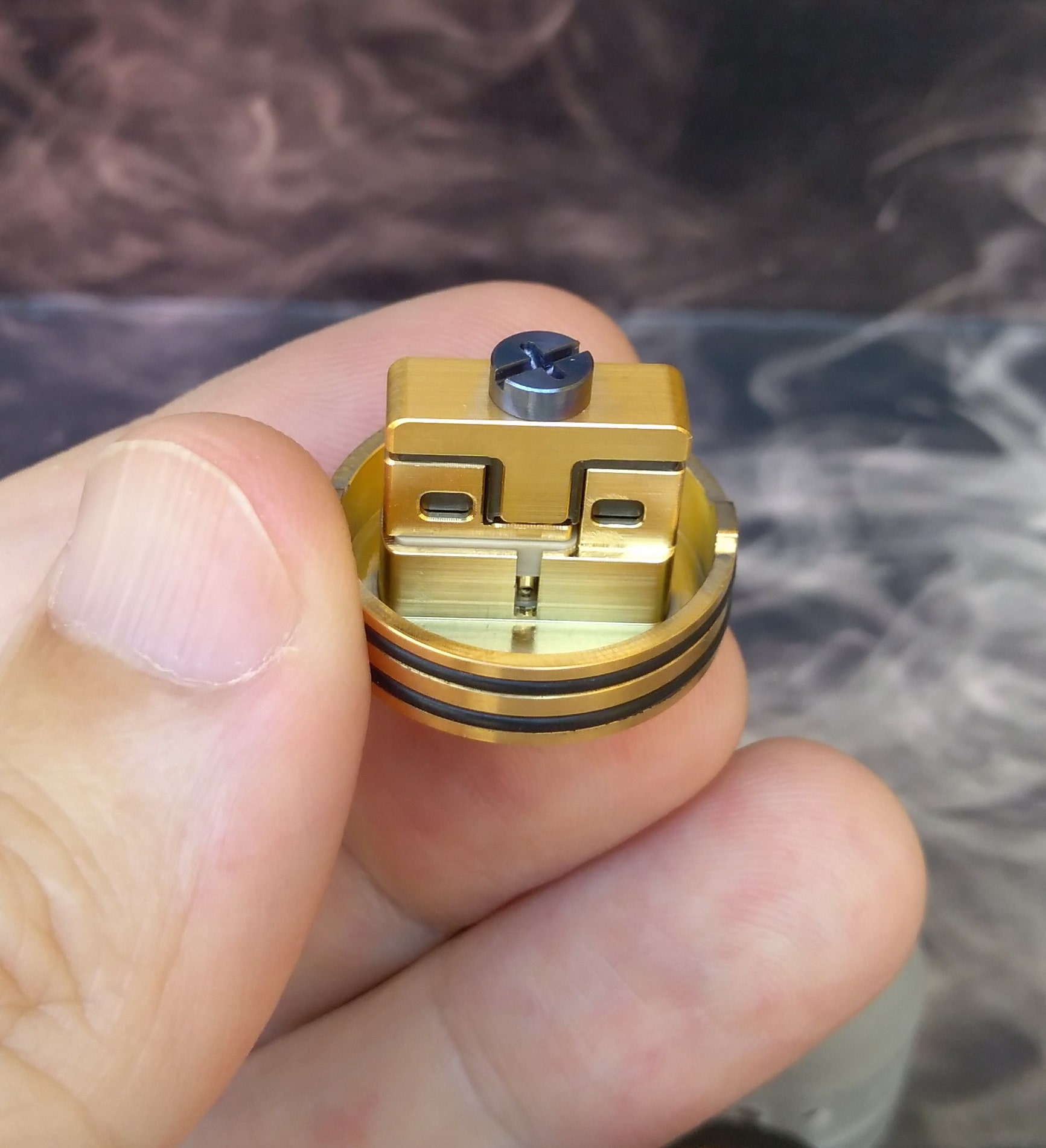 My version has a nice matte black aluminum anodized top cap. Both finishes have a solid quality 810 drip tip, a 24K gold-plated build deck and a superb quality clamp snag one piece coil post. Both regular and the squonk pin are gold plated brass and the extra frosted bullet-shaped single piece top cap is PC.